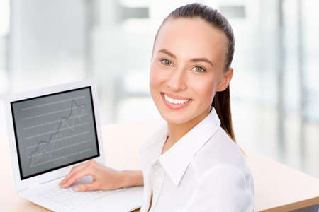 Portrait of smiling business woman working with laptop Stock Photo - 14858186