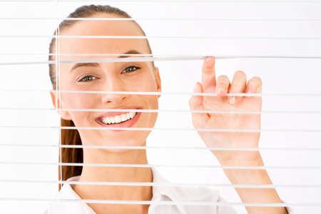 Happy business woman peeking through a venetian blind in an office photo