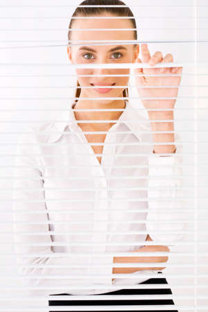 Happy business woman peeking through a venetian blind in an office photo