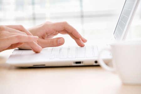 teclado de computadora: Primer plano de los dedos femeninos que pulsan un documento de negocios en el ordenador portátil