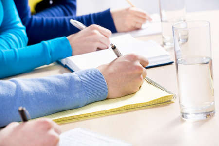 executive courses: Close-up peoples hands writing something during lecture