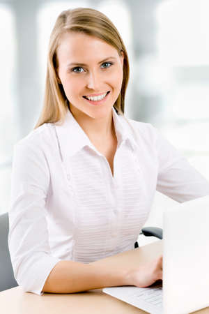 Business woman working on laptop computer at office Stock Photo - 14919878