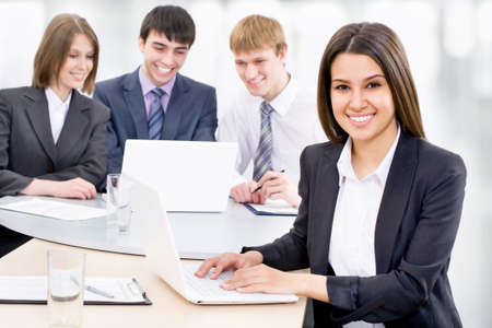 young women only: Portrait of attractive smiling business woman, team in background