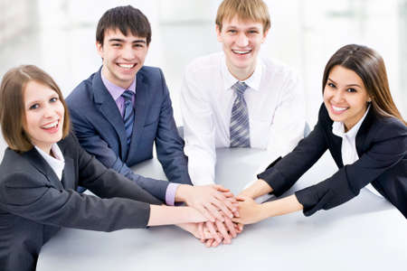 consensus: Top view of happy business team with their hands together gesturing unity