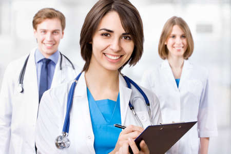 consultant physicians: Young female doctor and her colleagues Stock Photo