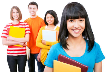 Happy young teenager students standing and smiling with books photo