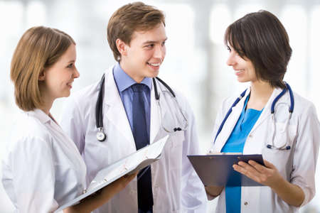Attractive doctor with his young colleagues Stock Photo - 15115634