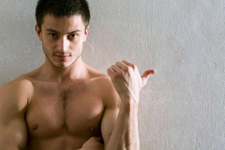 anatomy nude: Portrait of muscular man who is pointing a finger at a gray wall  Stock Photo