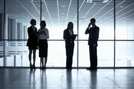 business woman standing: Business people silhouettes in a modern office
