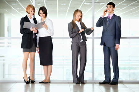 Full length portrait of professional business people discussing reports in a office corridor Imagens
