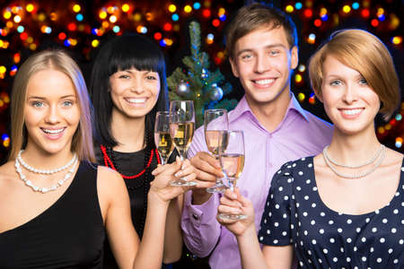 company party: Portrait of smart colleagues with flutes of champagne wishing you Merry Christmas
