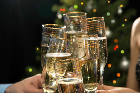 personas festejando: Feliz Navidad. Imagen de las manos de las personas con copas de cristal llenas de champán