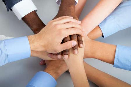 negocios internacionales: Equipo de negocios internacional que muestra la unidad con las manos juntas Foto de archivo
