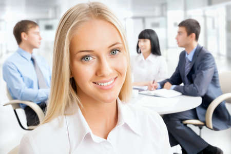 1 and group: Closeup portrait of attractive business woman smiling with colleagues working in background Stock Photo