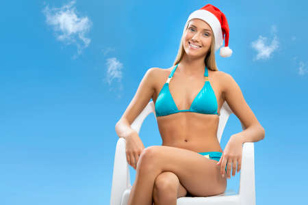Santa girl wearing Christmas hat on sky background photo