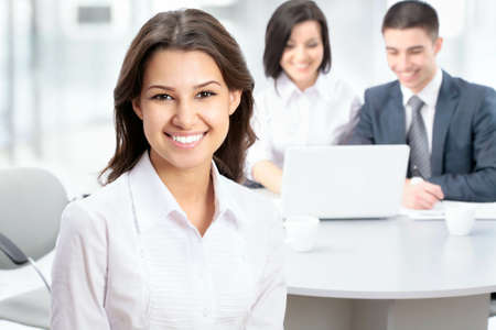 young office workers: Successful business woman sitting with her team at office