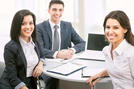desk work: Group of business people smiling in an office