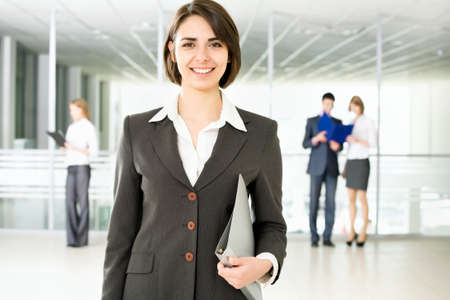 business woman standing: Business woman standing in front of her colleagues Stock Photo