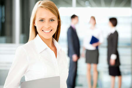 A business team with pretty business woman in front looking at camera
