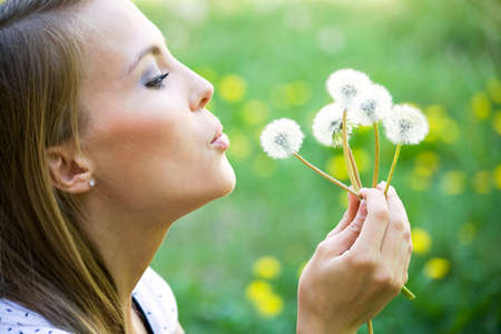 outsides: Young woman admiring dandelions Stock Photo