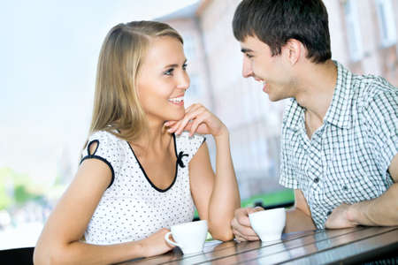 Beautiful young couple in love sitting at cafe photo