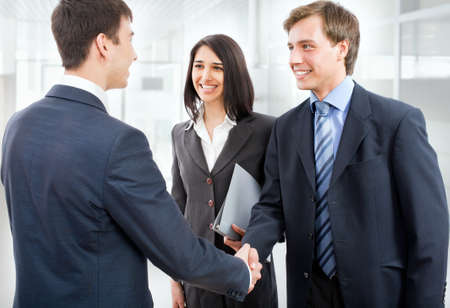 Business people shaking hands in modern office photo