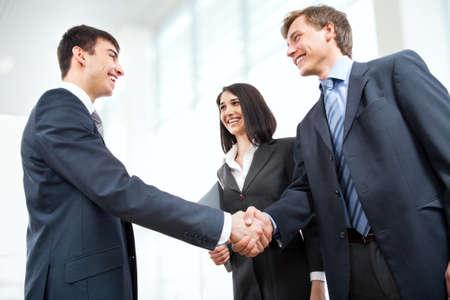 dandose la mano: Los hombres de negocios d�ndose la mano en la oficina moderna Foto de archivo