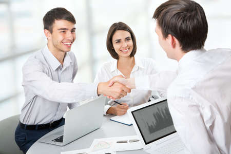 corporate meeting: Business people shaking hands, finishing up a meeting Stock Photo