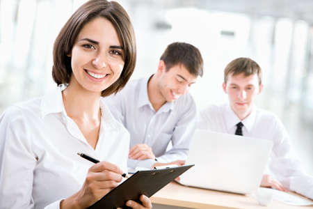 Successful business woman with her staff in background at office