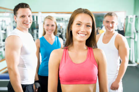 group plan: Woman smiling and standing in front of a group of gym people Stock Photo