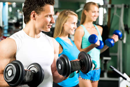 Women with  fitness trainer in the gym exercising with dumbbells photo