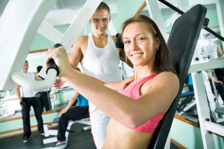 weight machine: Fitness. Woman at the gym doing arms exercises on a machine Stock Photo
