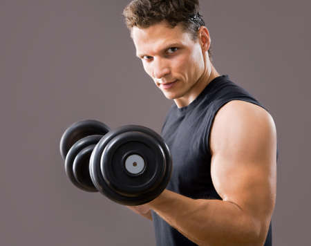 shirtless male: Fit muscular man exercising with dumbbell on gray background Stock Photo
