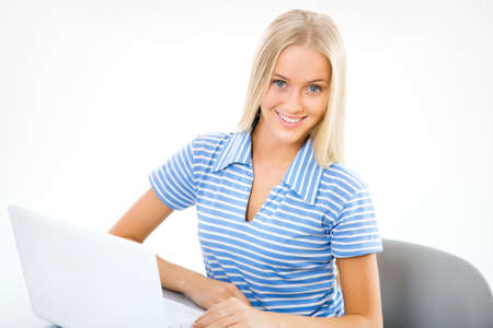 people sitting on chair: Portrait of young woman sitting on chair using laptop Stock Photo
