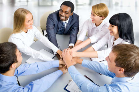 successful leadership: View from above of business team making pile of hands on working place