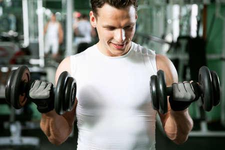 Homem com equipamento de treinamento do peso na sport club ginásio