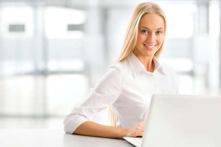 rubia: Retrato de una joven mujer de negocios usando la computadora port?l en la oficina