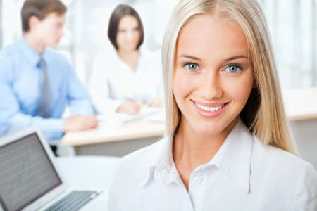 corporate training: Closeup portrait of attractive business woman smiling with colleagues working in background Stock Photo