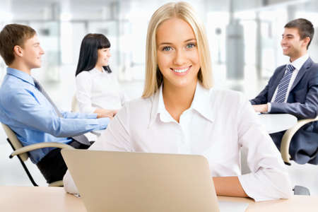 education success: Closeup portrait of attractive business woman smiling with colleagues working in background Stock Photo