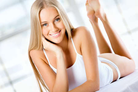 woman lying in bed: Beautiful blonde woman lying on the bed and smiling
