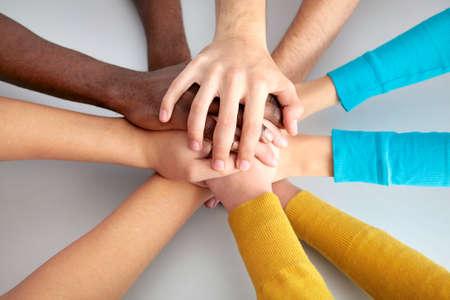 manos juntas: Alta vista de un equipo de amigos que muestra la unidad con las manos juntas