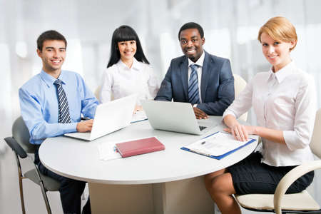 workplace wellness: Group of happy business people in a meeting at office
