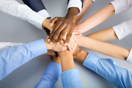 team leader: International  business team showing unity with their hands together Stock Photo