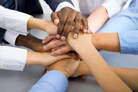 manos juntas: Equipo de negocios internacional que muestra la unidad con las manos juntas Foto de archivo