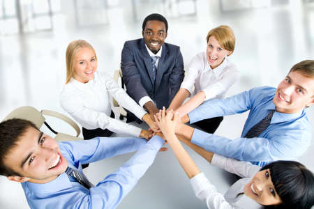 team victory: International  business team showing unity with their hands together Stock Photo