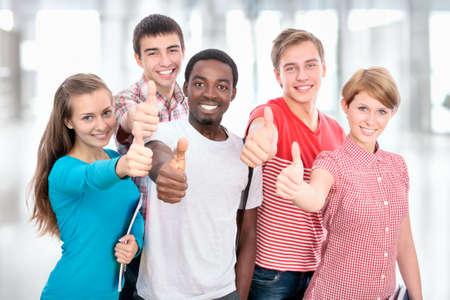 Feliz grupo internacional de estudiante muestra el pulgar hacia arriba