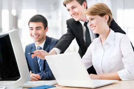 Young business people sitting at desk, using computer at business training, smiling. photo