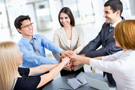 group goals: International  business team showing unity with their hands together Stock Photo