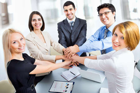 life support: International  business team showing unity with their hands together Stock Photo