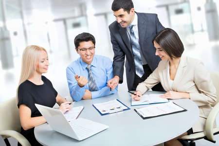 team problems: A business team of four plan work in office Stock Photo